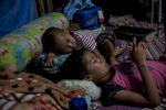 Sai Muang's children rest in their hut in a migrant construction camp. The family removed them from school to save money following his accident.