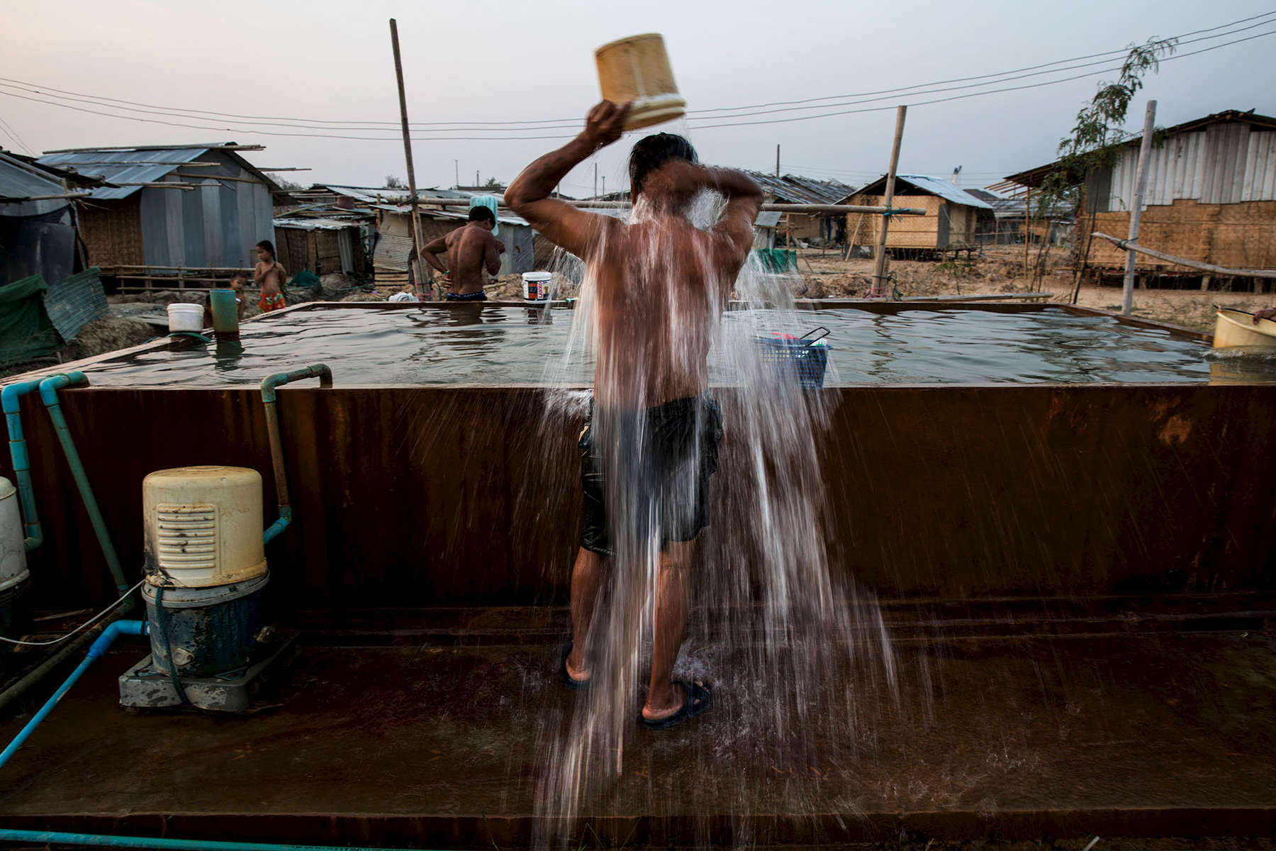 Migrants wash from a communal water basin shared by the entire camp of  approximately 200 people.