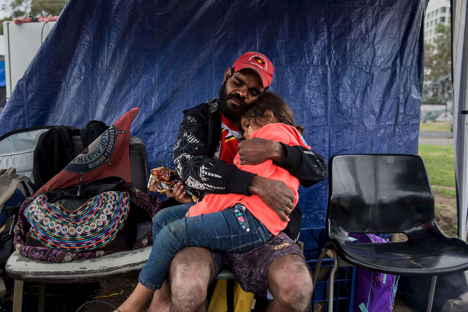 Stedman hold his daughter at the Redfern Aboriginal Tent Emabassy protest site in Sydney.