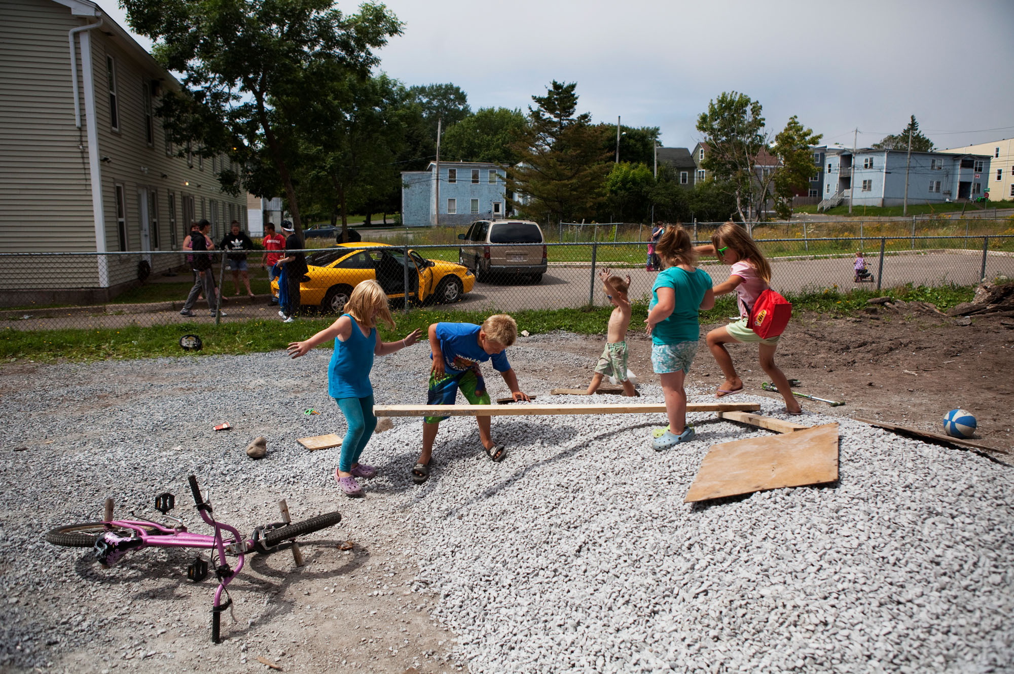 Children play in a gravel pile outside of their homes.
