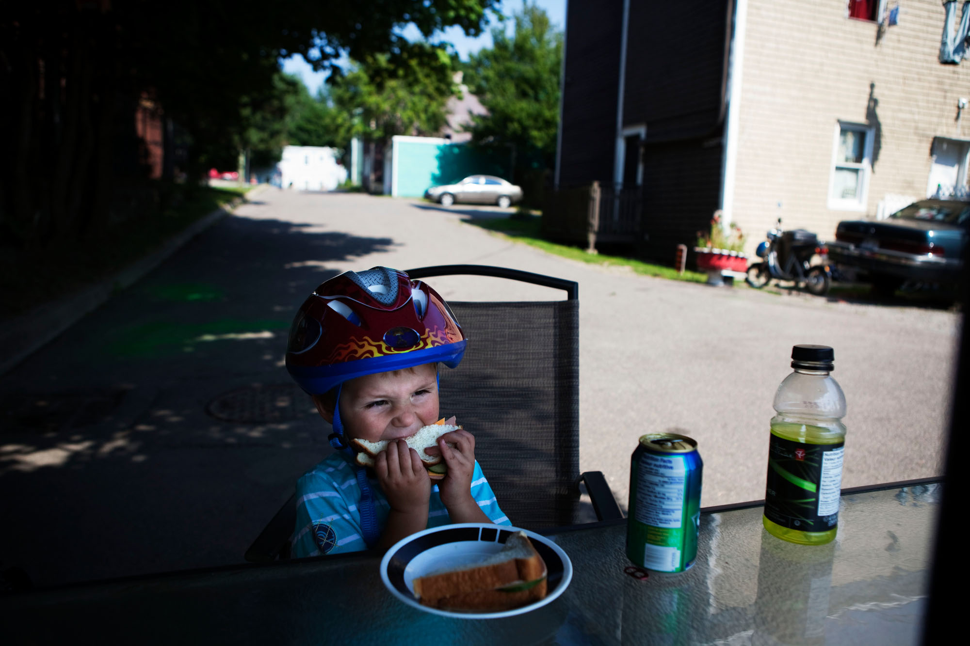 Dallas Kelly, 3, eats a sandwich outside of his home. Dallas and his mother, Melissa Kelly, recently moved to Saint John from Edmonton so that she could be closer to her daughter. {quote}I don't really care for the neighbourhood,{quote} says Melissa. {quote}It looks like garbage disposal hasn't been here in a while.{quote}