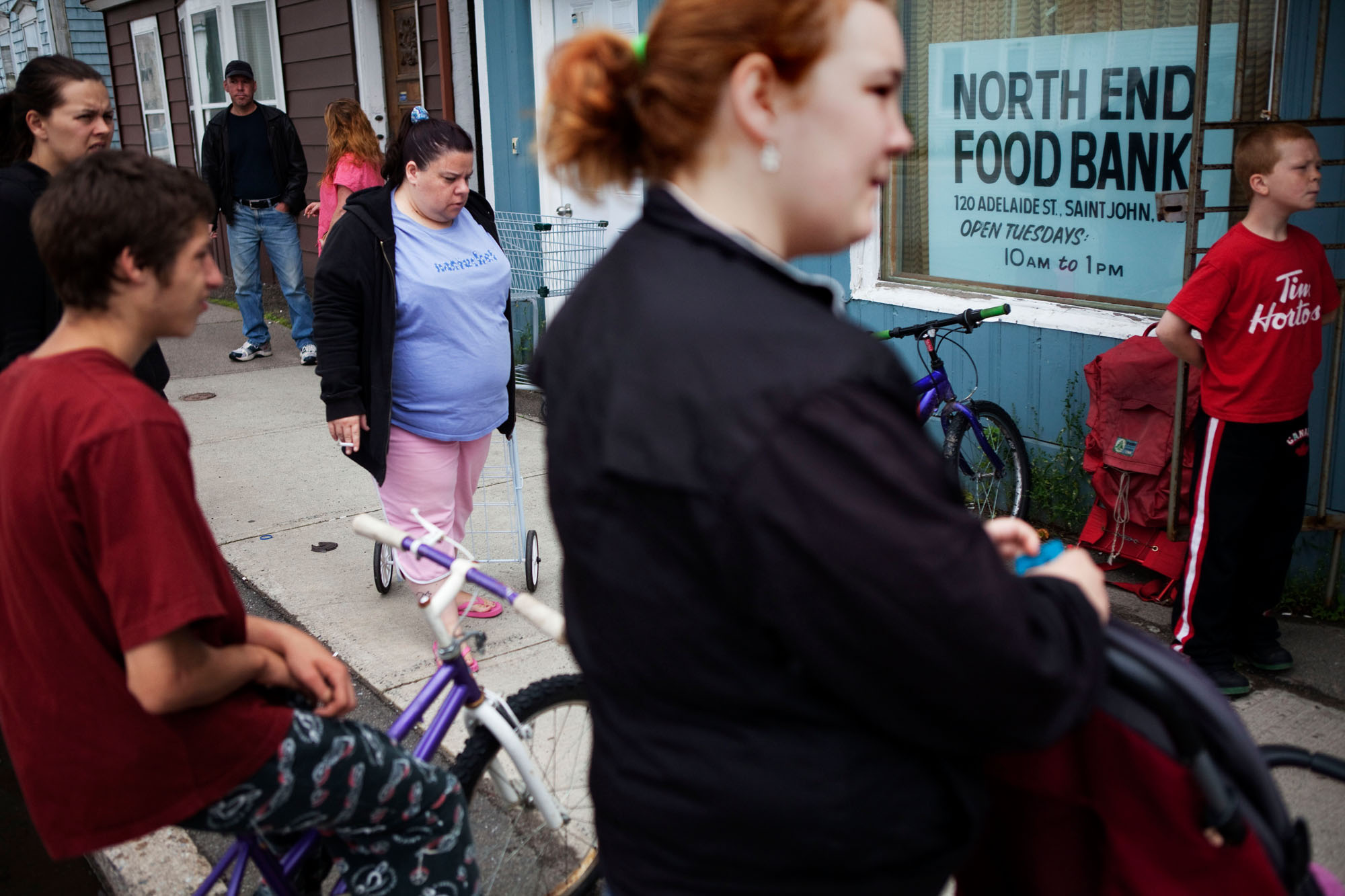 People wait for their numbers to be called at the food bank on Adelaide Street.