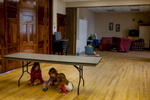 Girls play under a table during a free lunch at the Hope Mission in the Main St. Baptist Church.