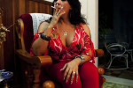 A transgender woman who has had breast implants smokes a cigarette at her friend's house.