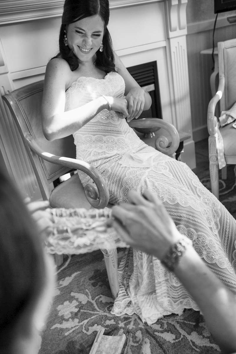 Laughing bride taking a moment to relax while she gets ready to walk down the aisle.