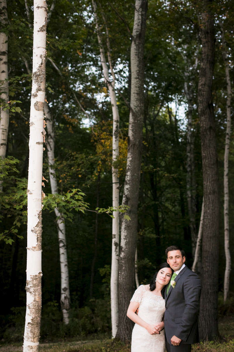 The bride and groom stare off into the gorgeous vermont woods at their Shrewsbury wedding.