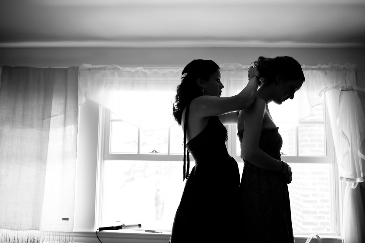 bride and bridesmaid get ready at a wedding venue in maine. by vermont wedding photographer monica donovan.