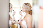 The bride applies her makeup in the mirror before she walks down the aisle in Charolotte VT.