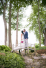 The newlyweds pause for a moment to kiss atop a rustic bridge in Grand Isle Vermont.