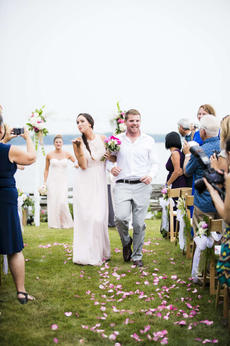 The new husband and wife greet their friends and family for the first time as a married couple in this intimate wedding photo taken by eve event photography.