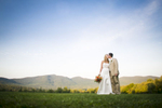 Gorgeous photo of the bride and groom kissing in front of the majestic Vermont mountains.