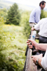Groomsman uncorks a craft beer before an Ohana Camp, Vermont wedding. by Vermont wedding photographers Eve Event Photography