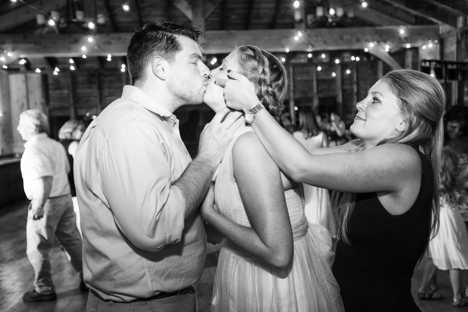 A wedding guest sneaks up on the newlyweds mid-kiss.
