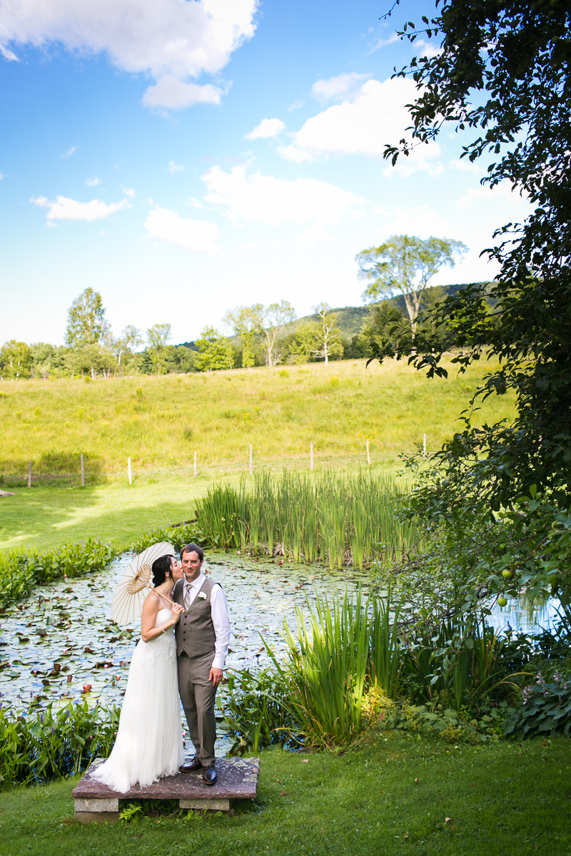 Bride and groom stand near a pond with a brilliant blue sky highlighting the Vermont mountains.