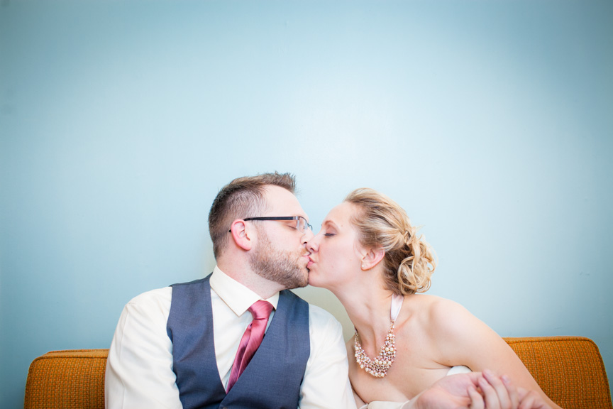 Bride and groom kiss in front of a blue wall at a Lebanon New Hampshire wedding. by vermont wedding photographers at Eve Event Photography