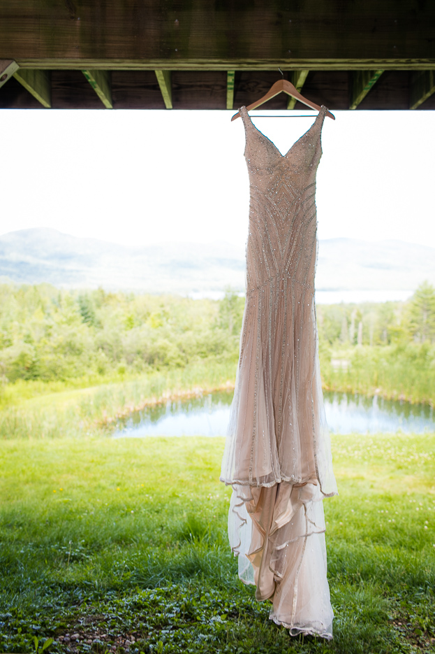 Stunning wedding dress hanging from a barn beam in front of a picturesque Vermont landscape.