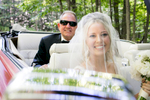 Gorgeous bride in a convertible with the father of the bride in the backseat.