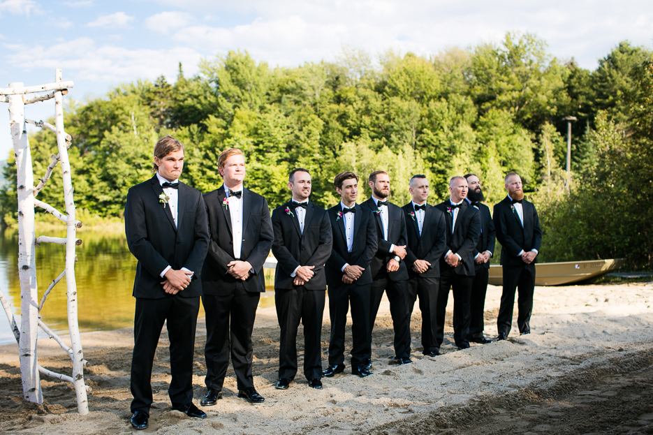 A line of groomsen flank the groom as he awaits the arrival of the stunning bride on the beach in Vermont.