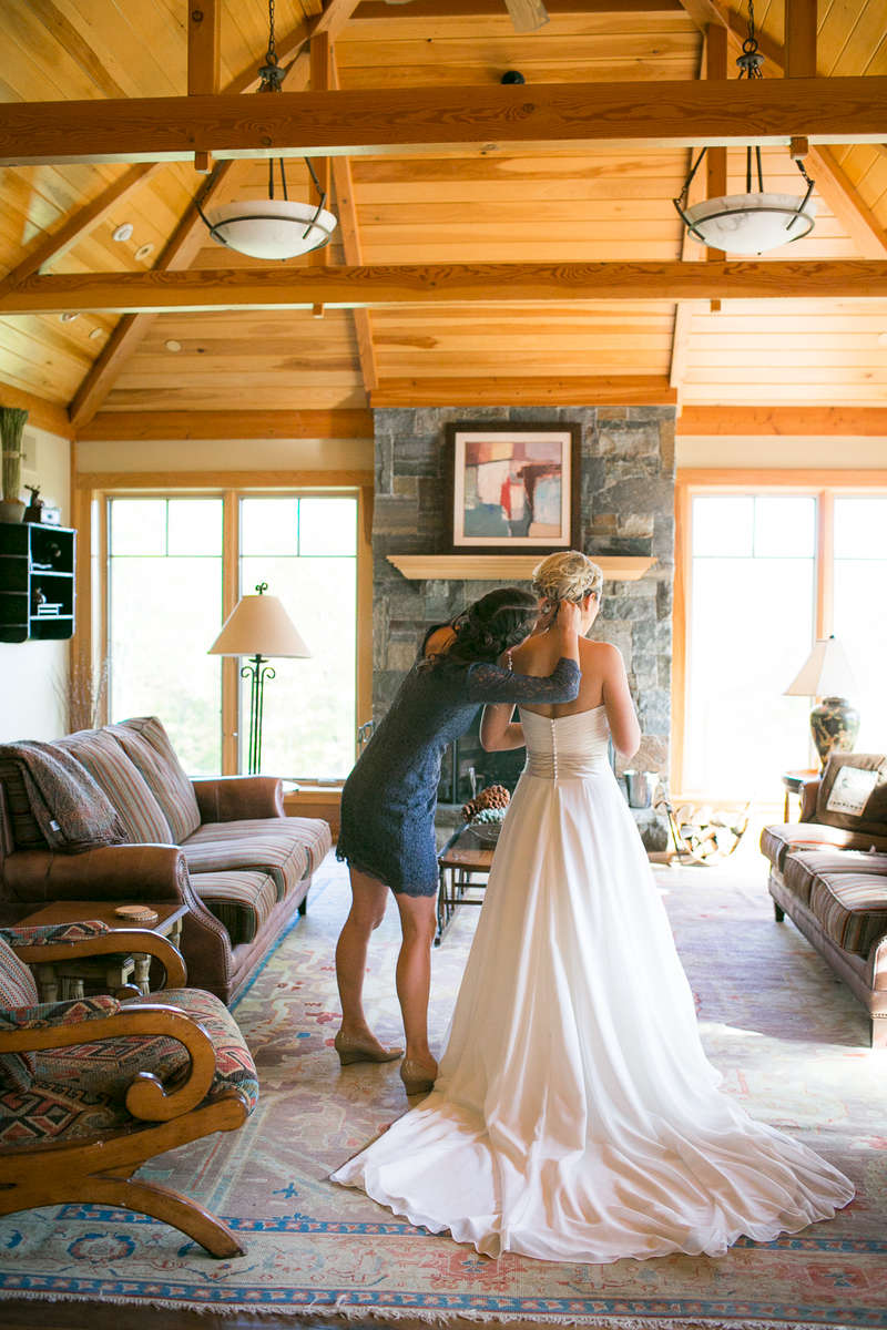 The bride gets some help getting ready in a rustic Vermont beam house at the Mountain Top Inn in Chittentdon.