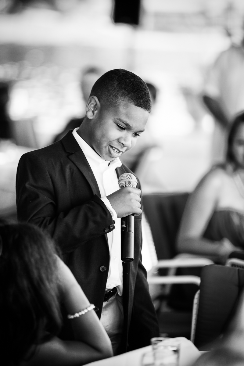 An adorable moment is caught on film as a young wedding guest gives his speech at this Le Bistro Du Lac wedding reception in upstate New York.