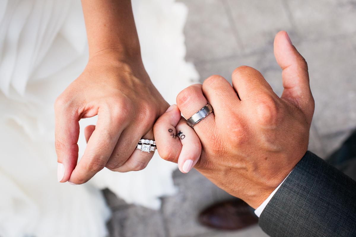 A bride and groom's hands, tattoos and wedding rings at a Stowe Mountain Lodge. Vermont wedding captured by photographers at Eve Event Photography .