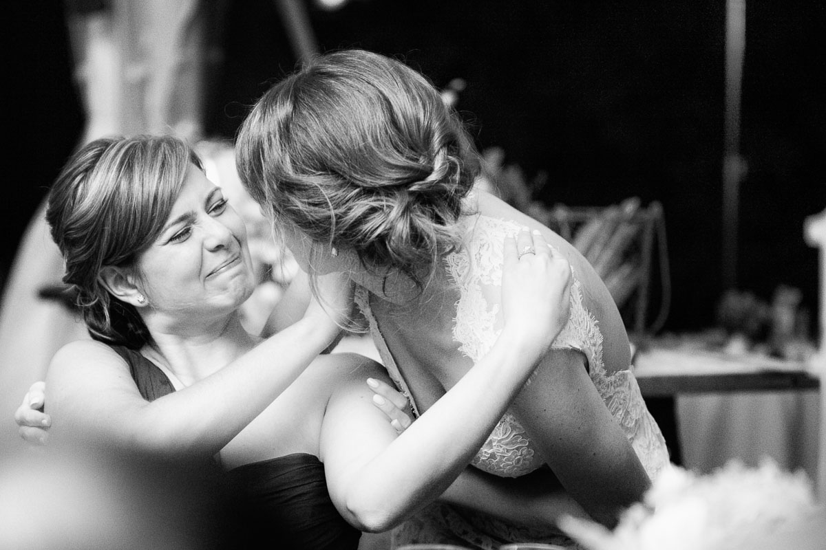 Vermont wedding photographers Eve Event Photography photograph an emotional moment between sisters at Fernbrook Farm, Bordentown New Jersey during toasts.