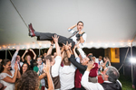 Brendan crowd surfs at his wedding reception at All Souls Interfaith Gathering in Shelburne, Vermont. by Vermont wedding photographers at Eve Event Photography