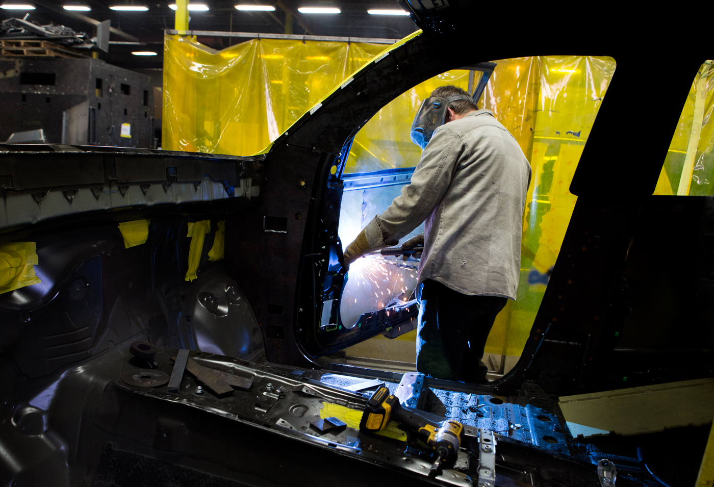 A welder adds armoring to a door at INKAS Armored Vehicle Manufacturing, for Manufacturing Automation magazine.