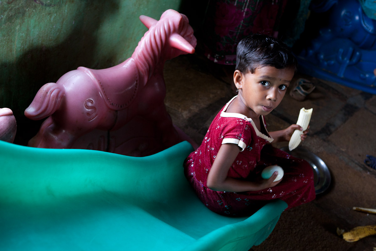An undernourished child enjoys her afternoon meal in her village classroom. For those fortunate to receive aid, these meals may save their lives.
