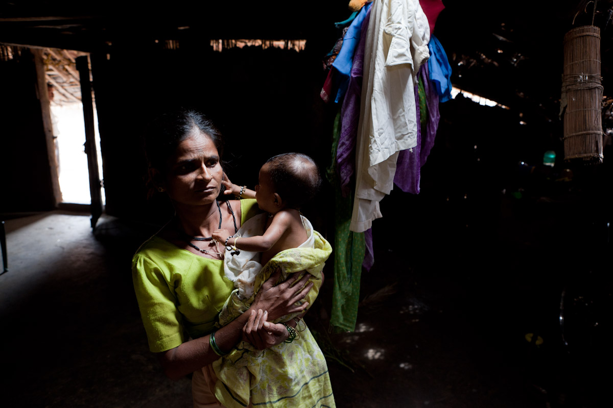 A mother holds her child who suffers from Grade III malnutrition in the Jawhar tribal belt of Northern Maharashtra. They share their home with their family cow who occupies the rear of the single room.