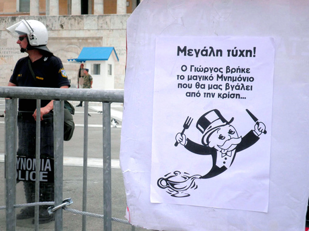 The cartoon attached to the barricade outside the Greek Parliament reads: {quote}Great Luck, George (Papandreou) has found the magic formula to get us out of the crisis.{quote}