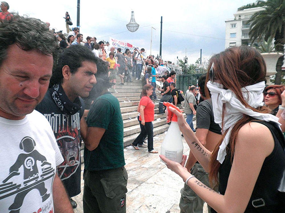 A first aid volunteer sprays a fellow protester with Maalox on the stairs leading into Syntagma Square.
