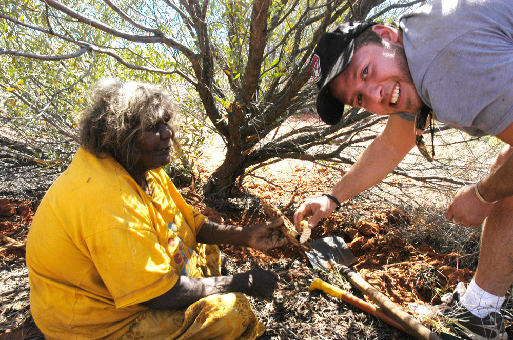 Mutitjulu elder Barbara Tjikatu, hands Elliot from Melbourne his first witchetty grub, during a cltural workshop on Aboriginal on Aboriginal land, central Australia.