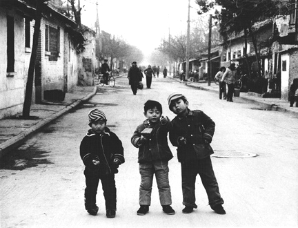 Three boys playing in the street outside their school in Xian province, China