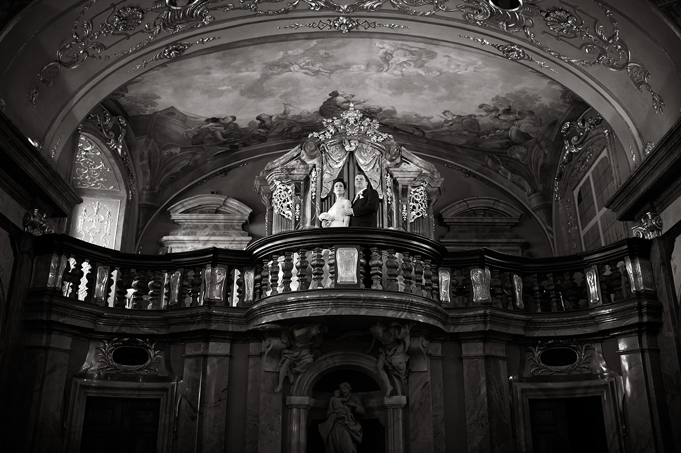 This is a black and white portrait of the bride and groom on the church choir of the Klementinum Mirror Chapel in Prague, Czechia. Prague weddings and elpments.