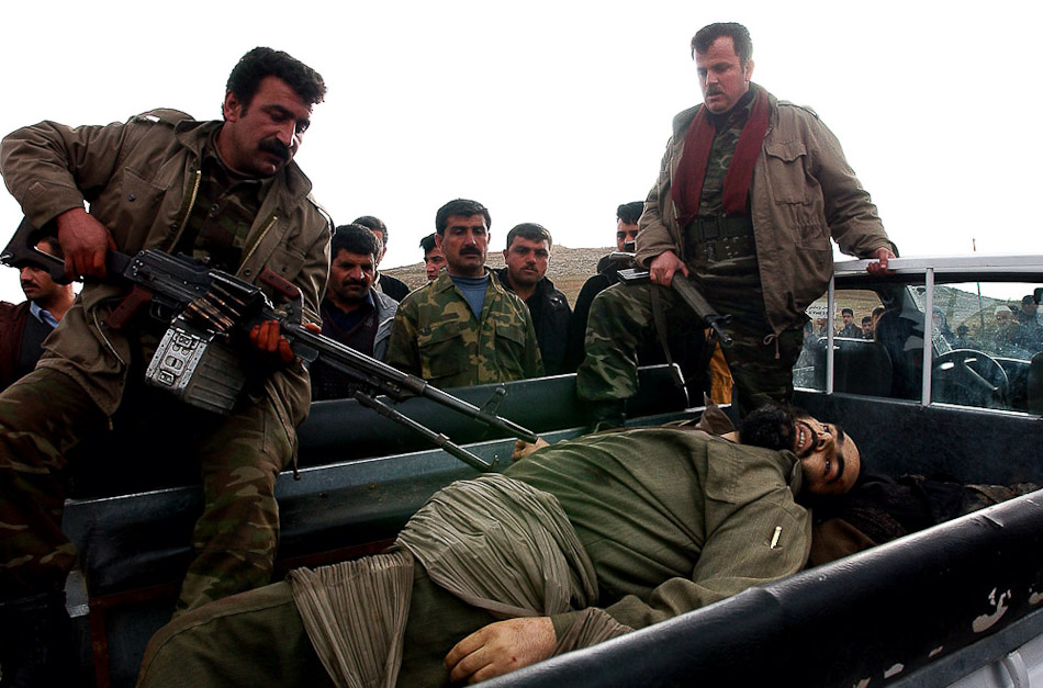 Kurdish authorities remove the bodies of five slain memebers of an Ansar al Islam splinter group at the Tasluga check point 20 km outside of Sulaimani in Kurdistan.
