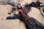 The bodies of five slain memebers of an Ansar al Islam splinter group lay on the ground before being taken away.