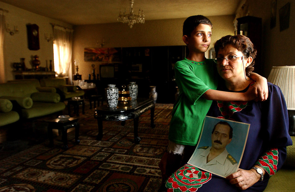 Amal Abdullah Mosul, with son, Yamour, age 7, searches for information about her missing husband, Hussain Ali Jihad, who was formerly a Brigadier in the Iraqi army. Hussain went missing on July 8.
