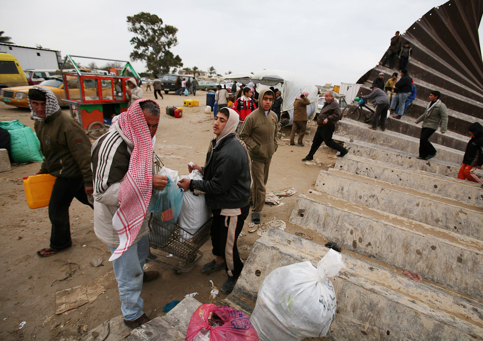 An estimated 700,000 Gazans crossed the Egyptian border to buy essential goods after Hamas blew open the metal and concrete border fence. The Redwan family used a shopping cart to transport their  purchase of food staples.