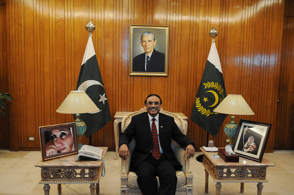 President Asif Ali Zardari poses next to two pictures of his deceased wife, Benazir Bhutto, in front of a picture of Jinnah, the founder of Pakistan.