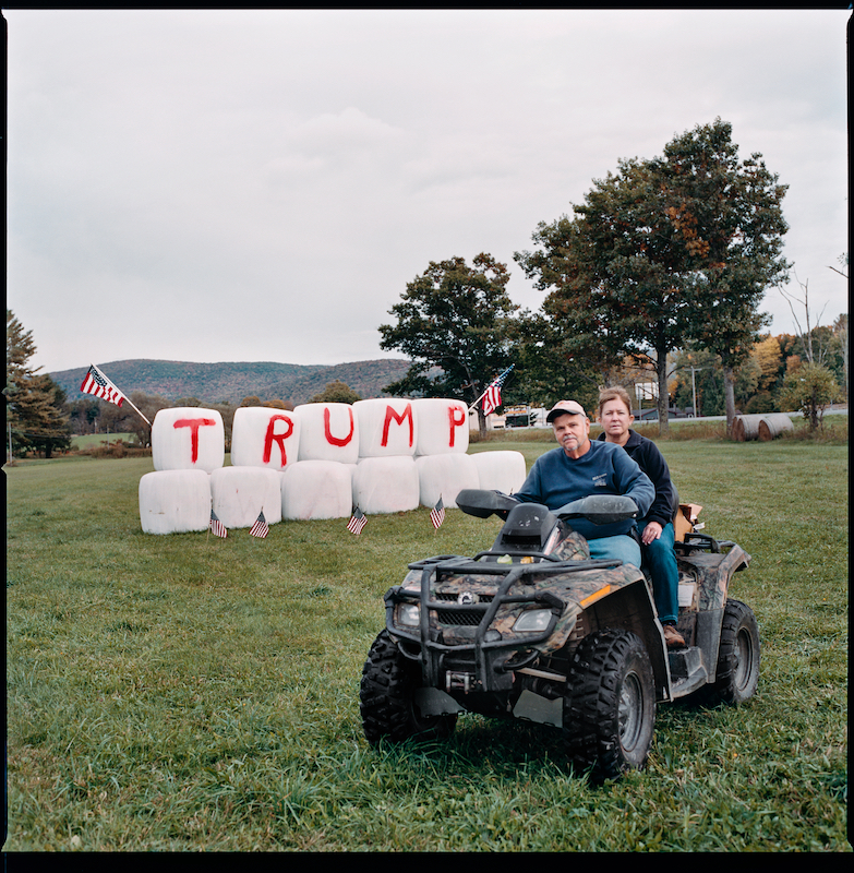 Neil and Susan Gardner, Stephentown, NY. October 9th 2016.Sign built in September 2016. Wrapped hay bales, spray paint, flags. Had numerous yard signs stolen.  {quote}Our country has gone to shit{quote}