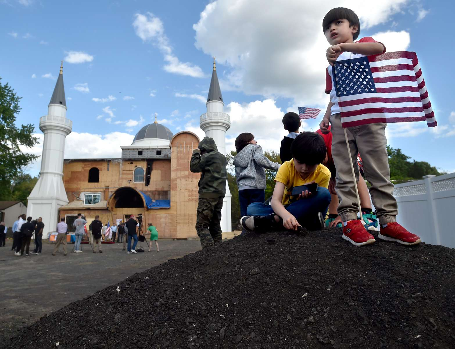 A boy holds an American flag  near the Diyanet Mosque in New Haven Thursday evening before a multi-faith gathering of solidarity organized by the Muslim Coalition of Connecticut. The mosque was damaged over the weekend by an arson-started blaze.