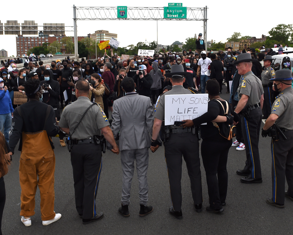 Hartford, CT - 6/1/20 - Connecticut State Police join hands with protesters on route I-84 Monday evening demanding action against police violence against people of color. Photo by Brad Horrigan | bhorrigan@courant.com