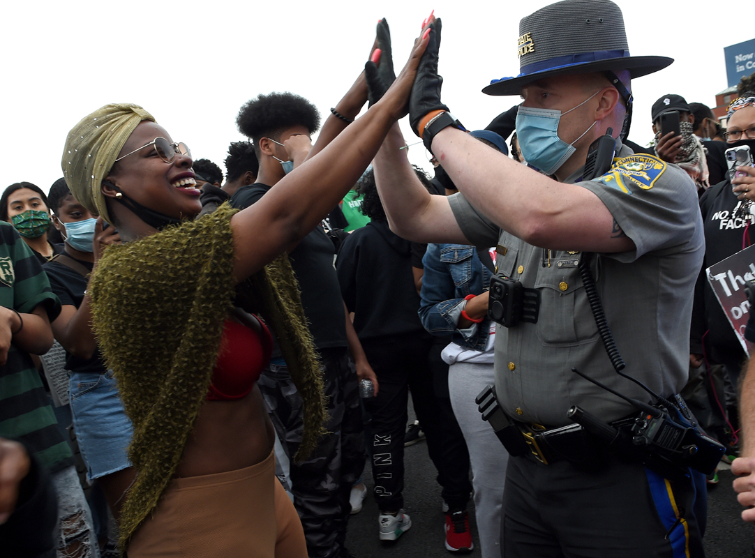 Hartford, CT - 6/1/20 - A protester, left, high fives Connecticut State Police Trooper First Class Richter after several troopers took a knee with protesters who had blocked Route I-84 Monday evening demanding action against police violence against people of color. Photo by Brad Horrigan   bhorrigan@courant.com