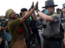 Hartford, CT - 6/1/20 - A protester, left, high fives Connecticut State Police Trooper First Class Richter after several troopers took a knee with protesters who had blocked Route I-84 Monday evening demanding action against police violence against people of color. Photo by Brad Horrigan | bhorrigan@courant.com