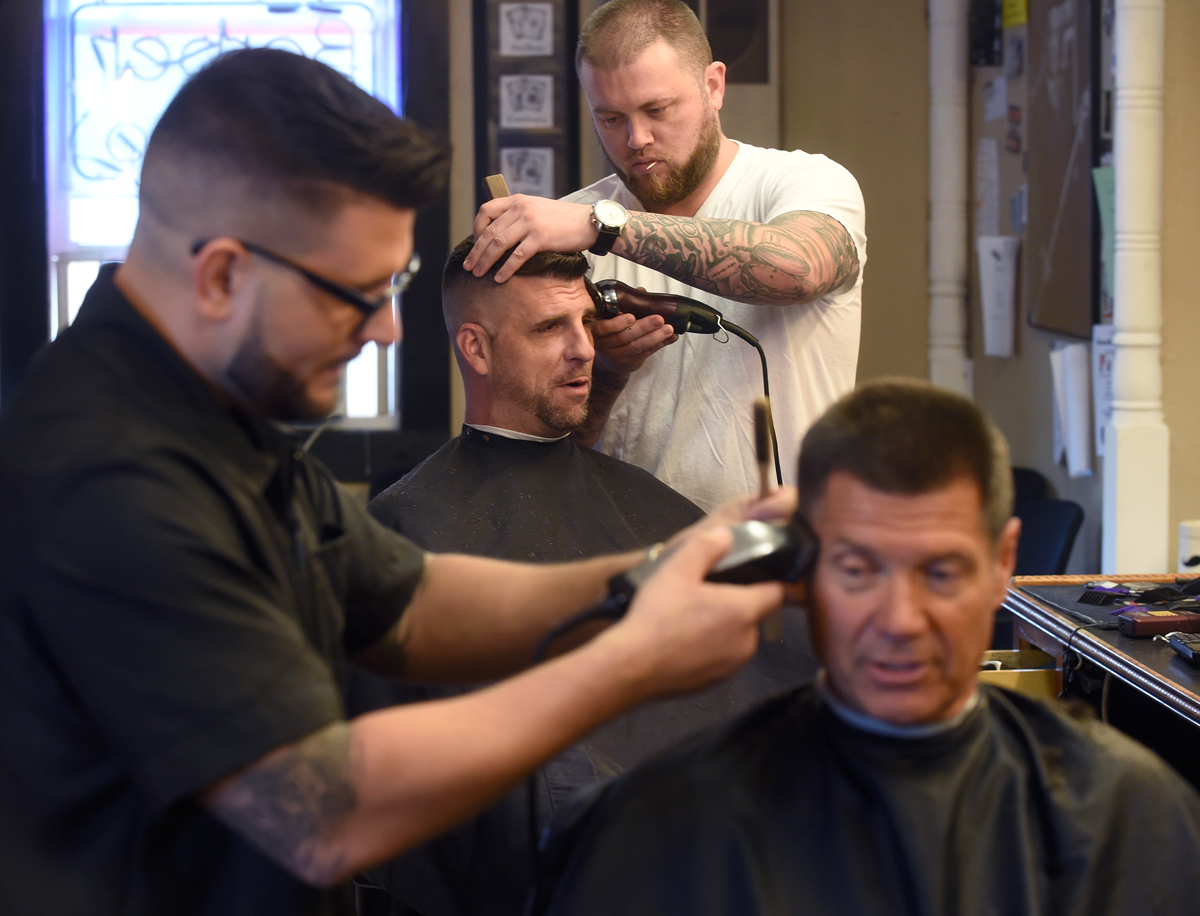 Ryan Howley, top, cuts Gene Wood's hair as Angelo Exarhoulias, left, cuts Jon Petrichenko's hair at The Barber Shop. Barbers and shop co-owners Hawley and Exarhoulias have now been in business together for 10 years and have been at the shop's current Brooklyn location for 4 years.
