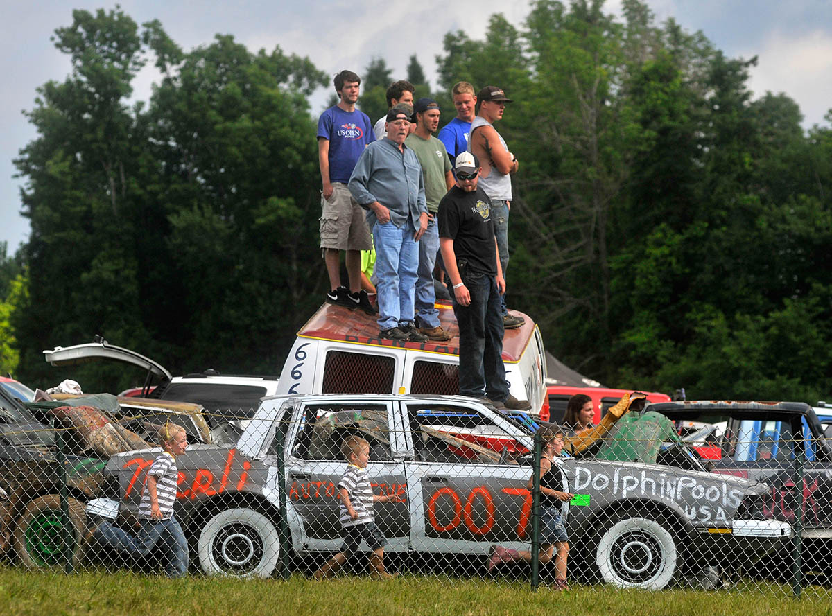Goshen, CT - 06/17/12 - Spectators of the demolition derby stand atop an already-demolished van at the Goshen Stampede at the Goshen Fairgrounds  Sunday.  BRAD HORRIGAN | bhorrigan@courant.com