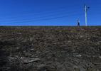 A man checks his phone will walking along a ridge at Great River Park in East Hartford Thursday.