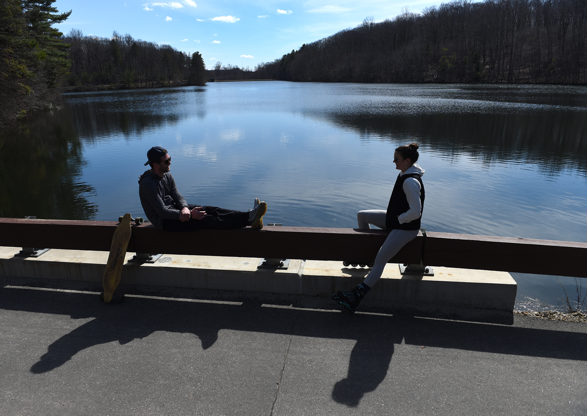 Two friends social distance at the West Hartford reservoir Wednesday afternoon. Both are residents of West Hartford.