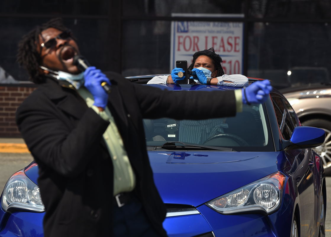 Octavia Velazquez, right, sings into a microphone while she live streams Urban Hope Refuge Church Easter drive-up service at Unity Plaza Sunday morning. Singing at right is Minister Ronald Campbell. During the COVID-19 pandemic, many houses of worship have taken to outdoor, drive-up services so social distancing can take place.